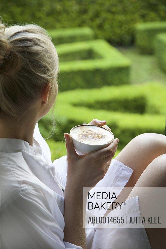 Woman Having Cappuccino Looking Out into Garden