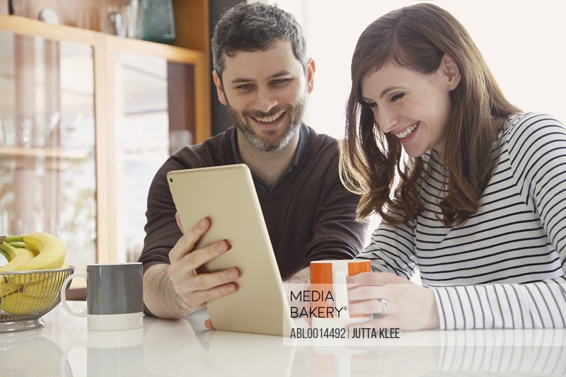 Couple Sitting at Table Using Digital Tablet Smiling