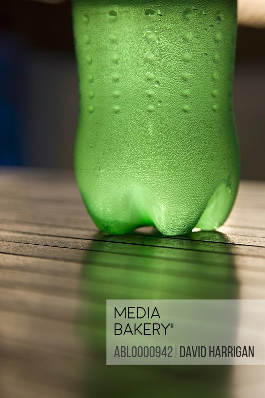 Close up of a green plastic bottle of cold water on a wooden table