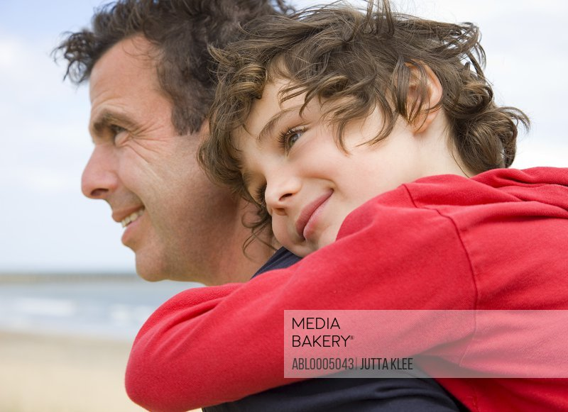 Close up of boy riding piggyback on his father shoulder