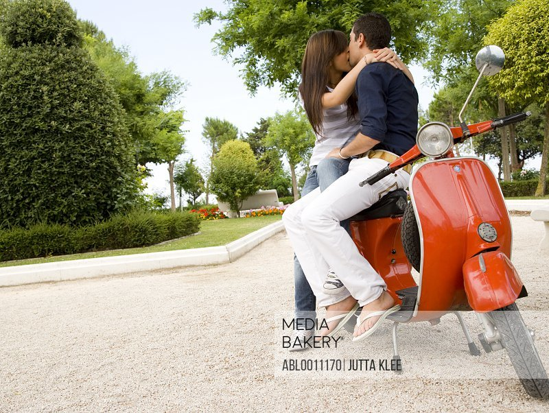 Portrait of young couple sitting on scooter kissing
