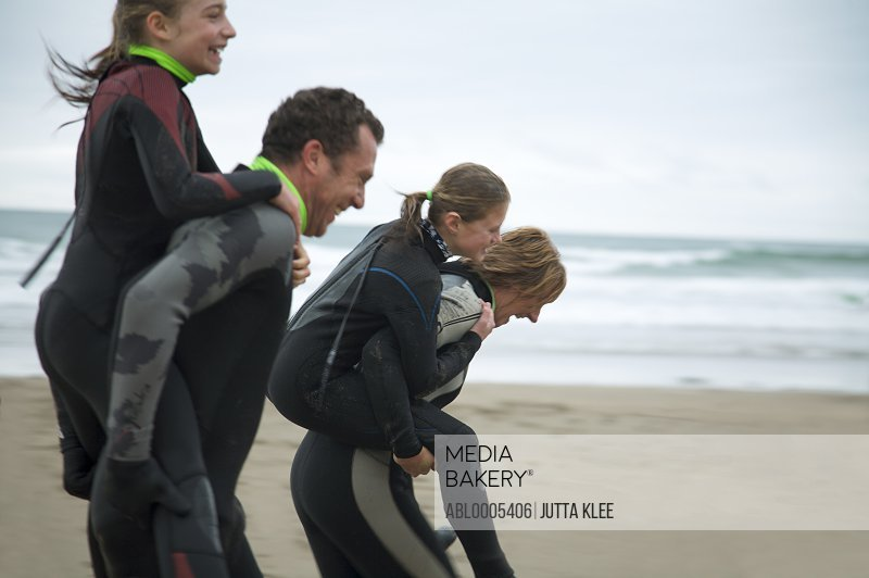 Man and woman wearing wetsuits running on a beach with two girls riding on their back