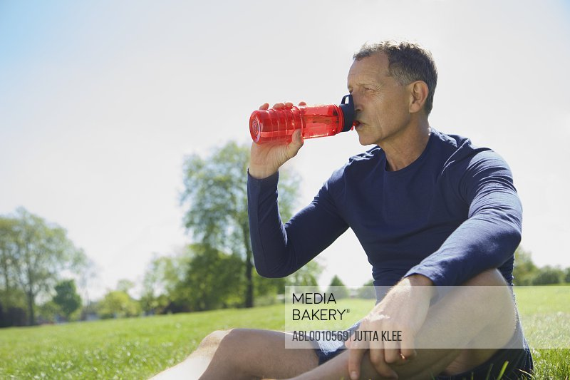 Mature Man Drinking from Water Bottle in Park