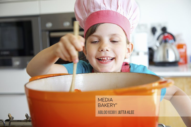 Smiling Girl Wearing Chef's Hat Stirring Casserole