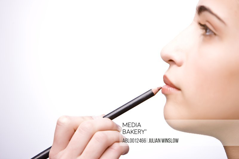 Profile of a young woman applying make on her lips with a lip pencil - close up