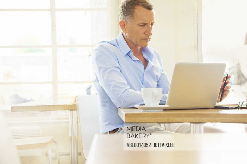 Mature Man Using Laptop in Cafe