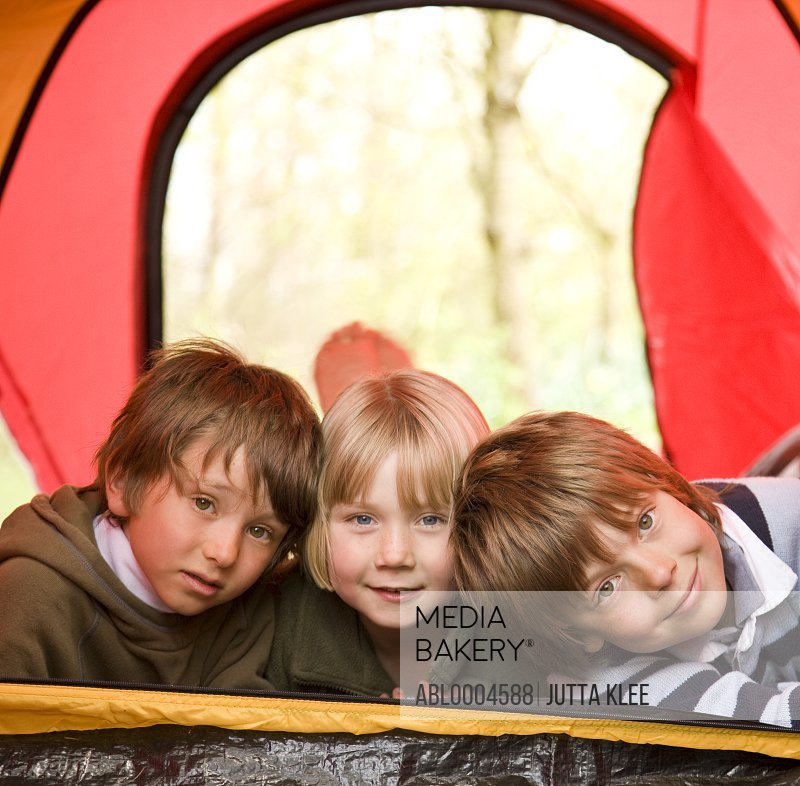 Portrait of three children lying in a tent