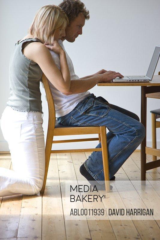 Woman kneeling behind man sitting and working on laptop computer