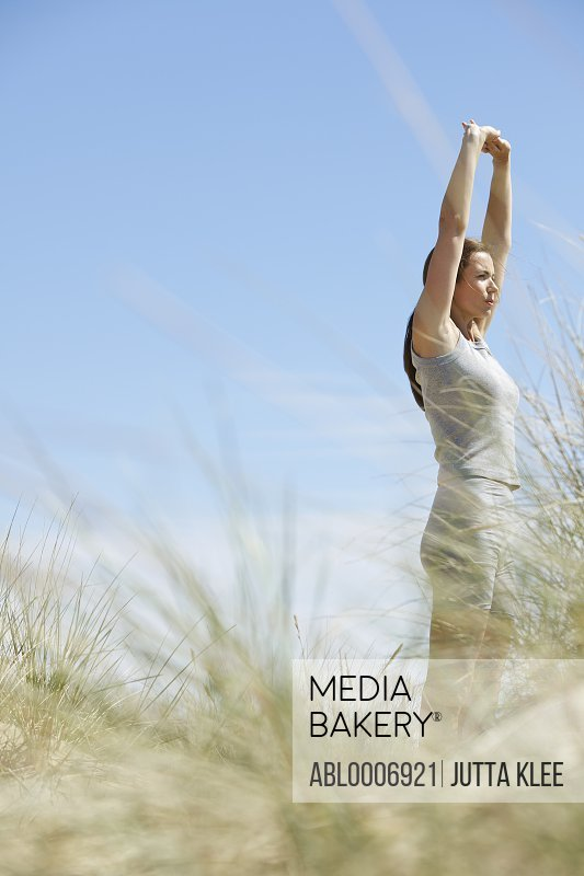 Woman Stretching Arms on Sand Dune