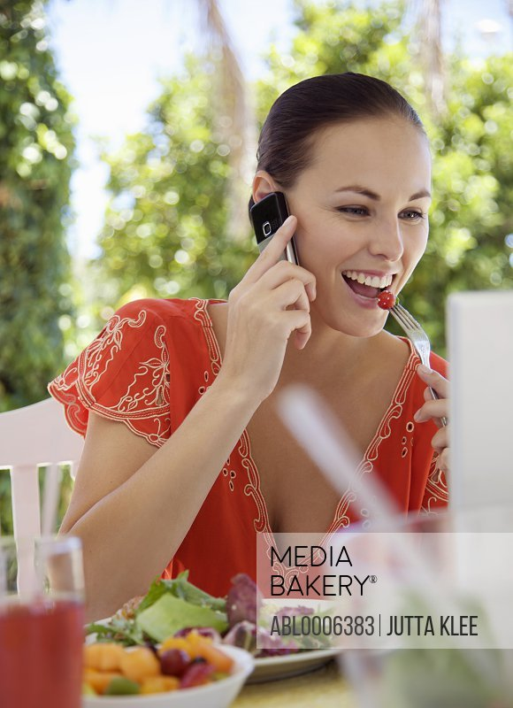 Smiling Woman on Cell Phone Having Lunch Outside
