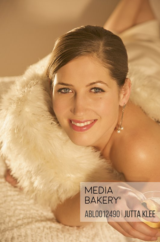 Woman wrapped in a swan feather stole holding a glass of champagne