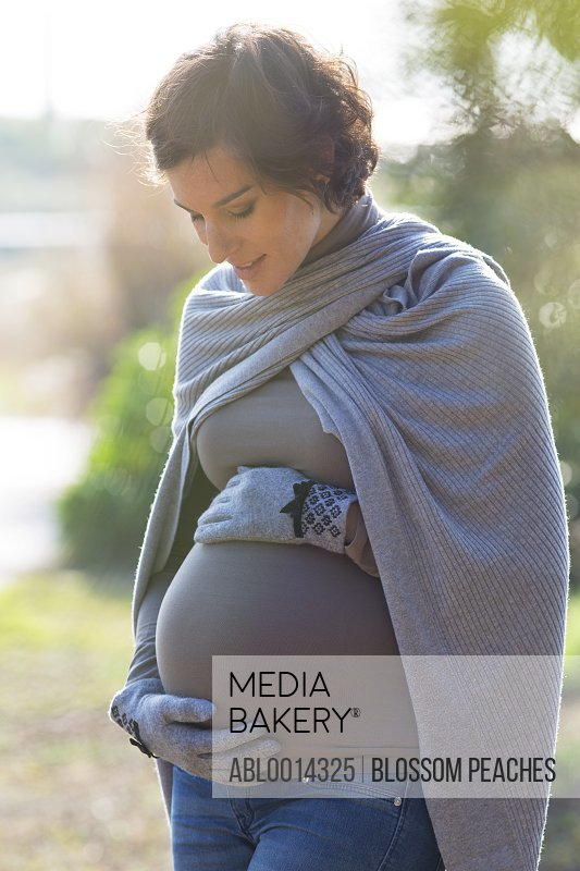 Pregnant Woman Holding her Stomach Outdoors