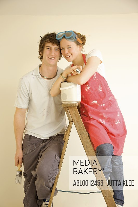 Smiling young couple leaning face to face on a ladder holding paintbrushes