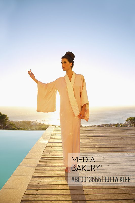 Woman Wearing Pink Kimono Standing with Hand Raised with Ocean in Background