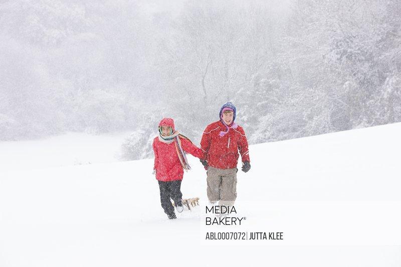 Boy and Girl Walking Through Snow Pulling Sledge