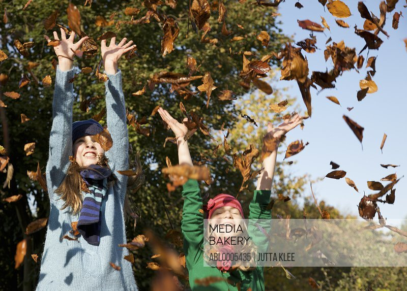 Two smiling girls throwing leaves in the air