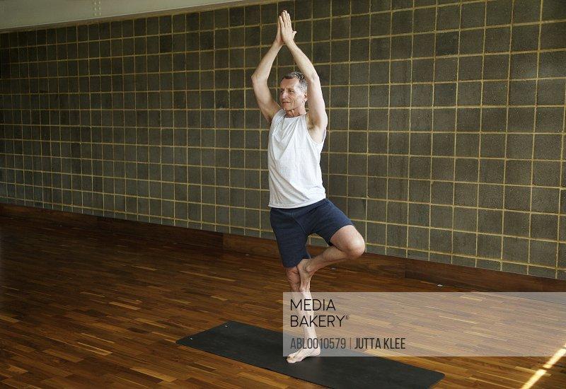 Mature Man Practicing Yoga, Tree pose