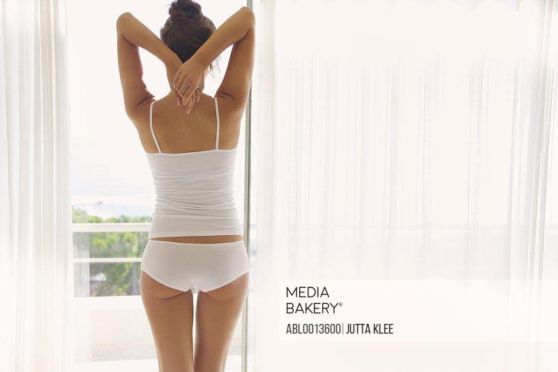 Woman Wearing Underwear Standing at Window
