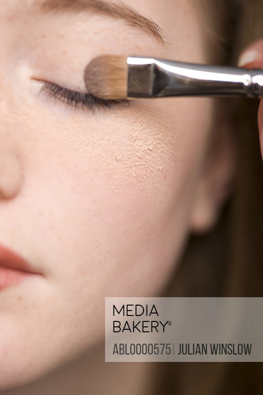 Woman applying eye make-up with eyeshadow brush and makeup powder under eye
