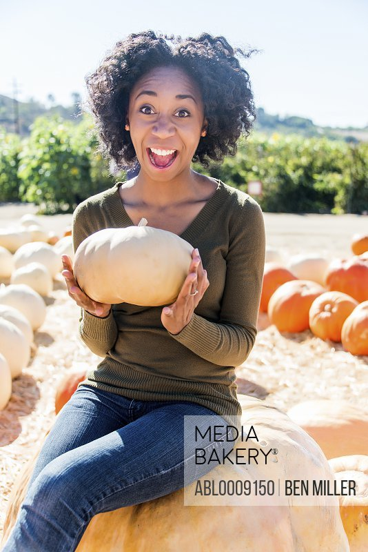African American Woman Sitting on Pumpkin Smiling in a Pumpkin Patch