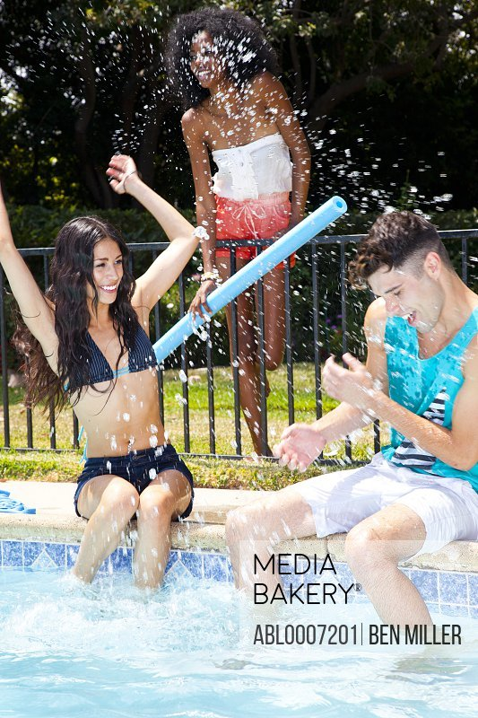 Woman Splashing Man by Swimming Pool
