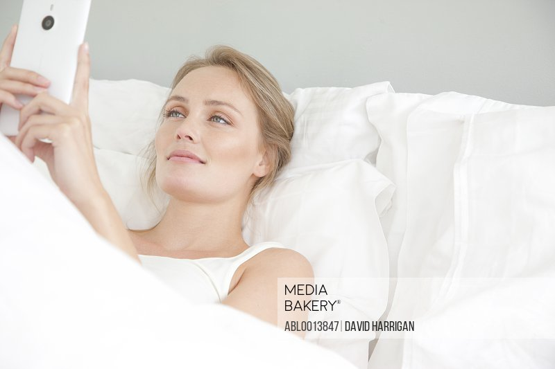 Woman In Bed Using Smart Phone