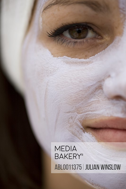 Extreme close up of young woman with mauve beauty mask