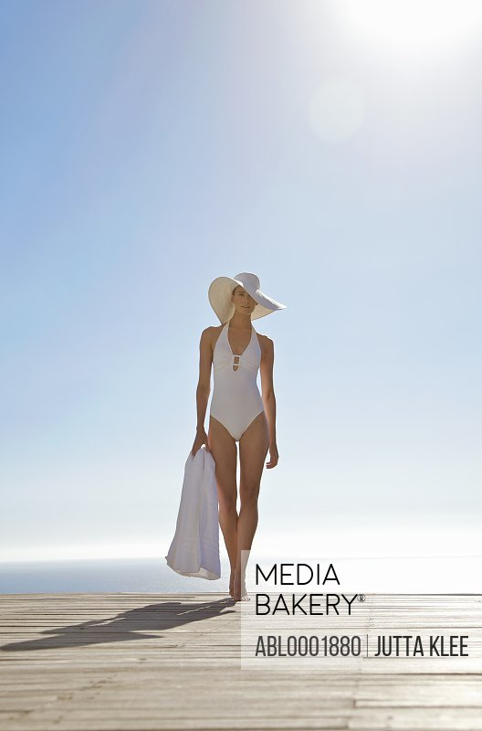 Woman in white hat and swimsuit standing on a sun deck holding a towel
