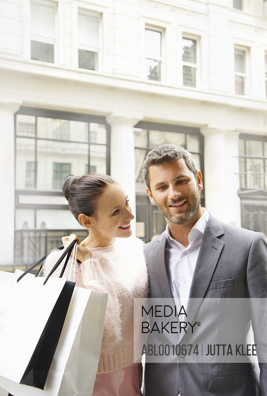 Smiling Couple on City Street with Shopping bags
