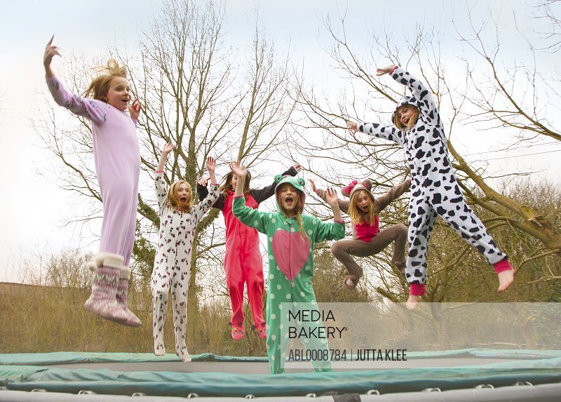 Group of Girls Wearing Animal Costumes Bouncing on Trampoline