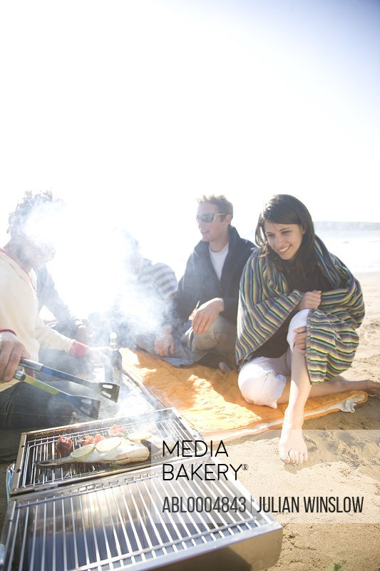 Friends sitting around a barbeque on the beach