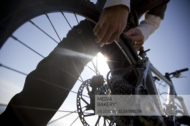 Man hands checking the wheel of a bicycle