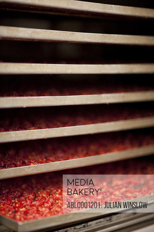 Close up of stacked drying racks filled with sun dried tomatoes