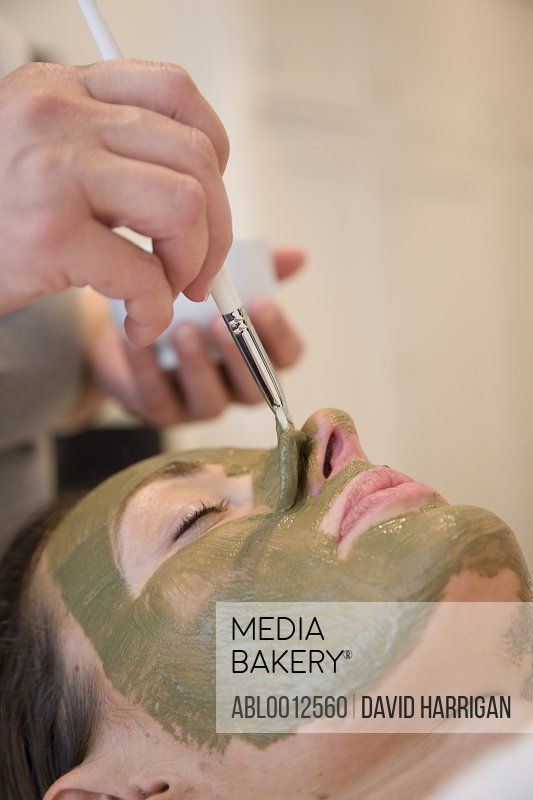 Beautician hand applying green facial mask on woman face with brush