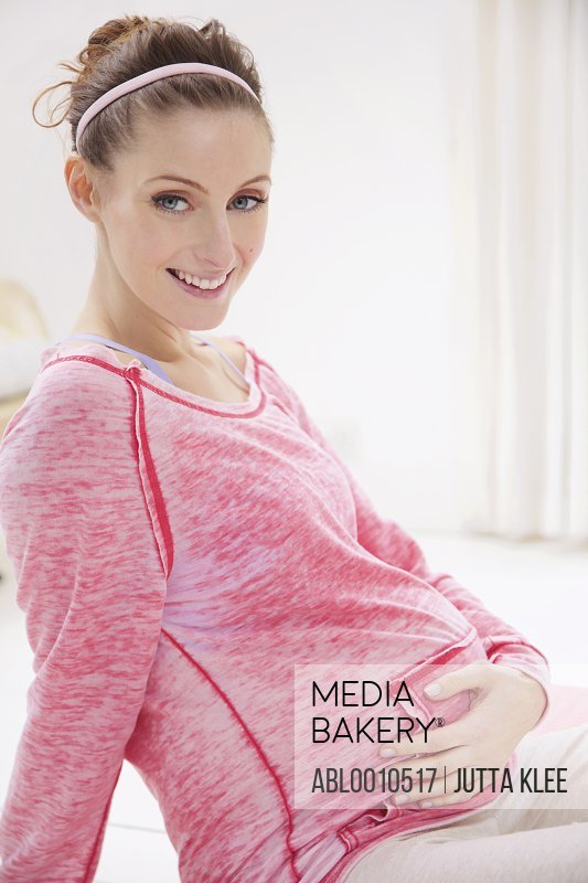 Smiling Pregnant Woman Holding her Stomach
