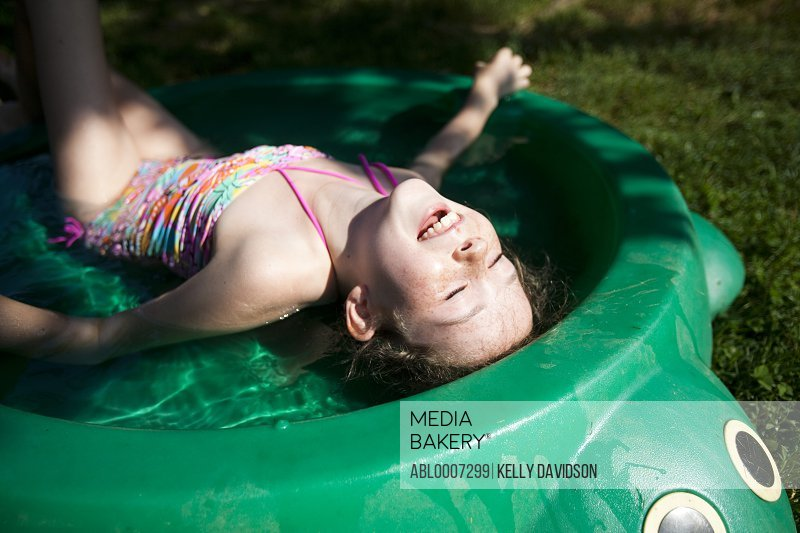 Smiling Girl Lying in Paddling Pool