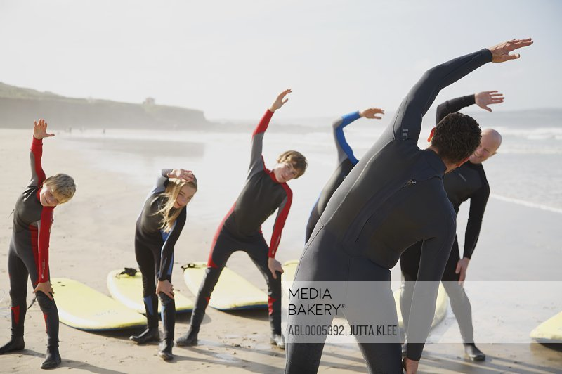 Back view of a surfing instructor and a group of students stretching on a beach