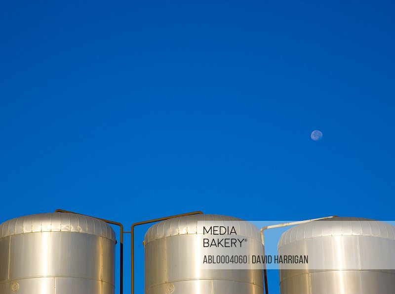 Metal storage tanks against a cloudless blue sky with moon