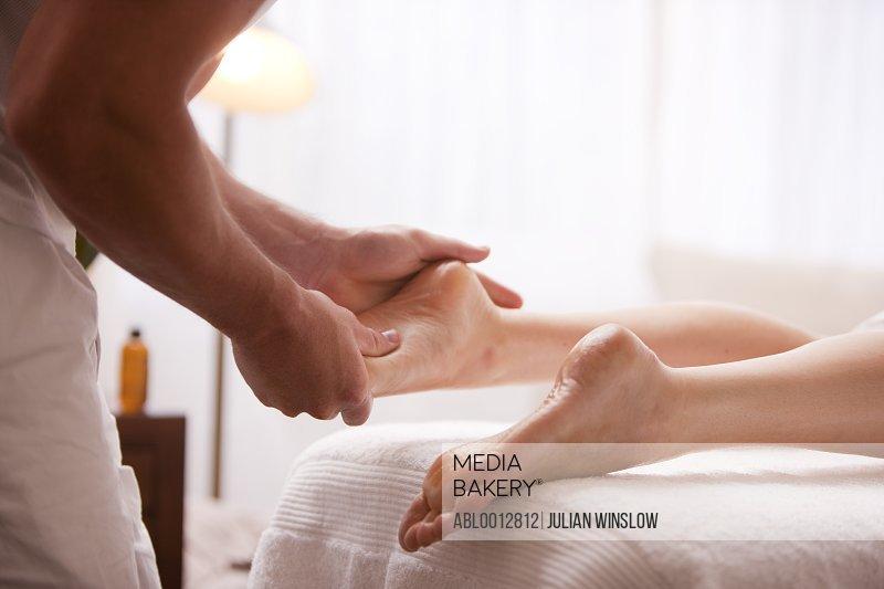 Close up of a masseur hands massaging a woman foot