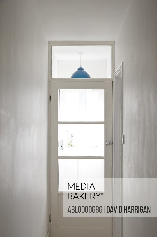 Narrow white hallway with glass door and blue lampshade