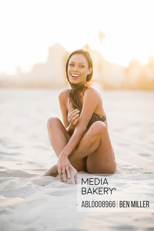 Smiling Woman on Beach Sitting on Sand