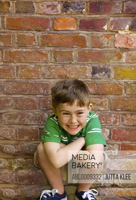Boy Crouching in front of Brick Wall Grinning