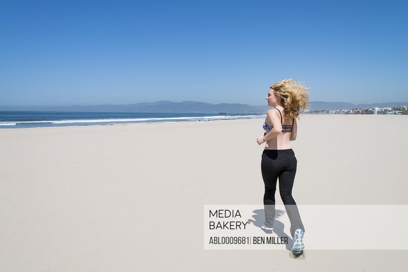 Young Woman Running on Beach, Back View