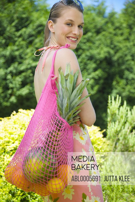 Smiling young woman carrying a shopping bag full of fruit