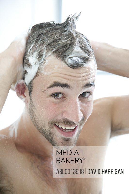 Smiling Man Washing Hair in Shower
