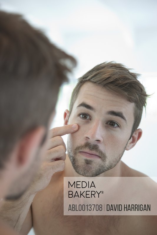 Man Looking in Mirror Checking his Face