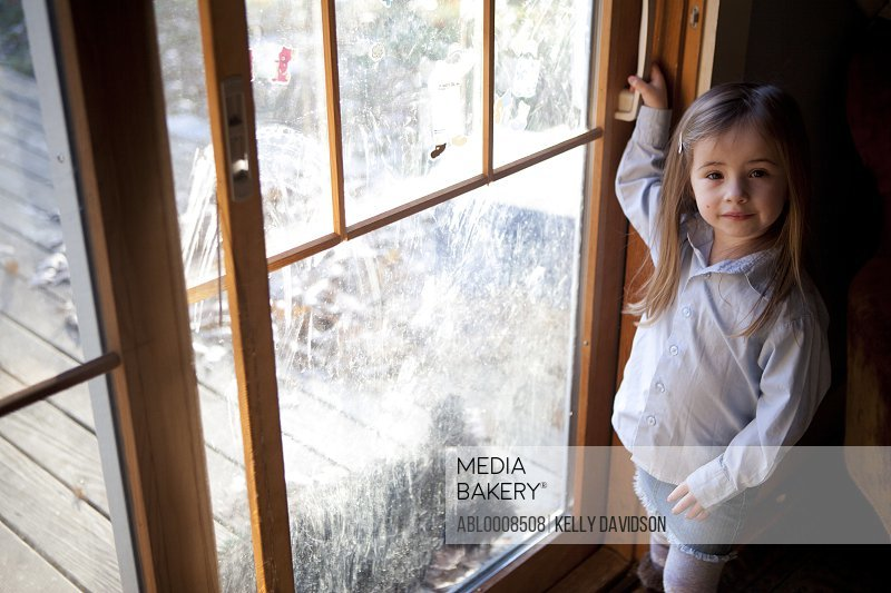 Young Girl Standing by Dirty Window