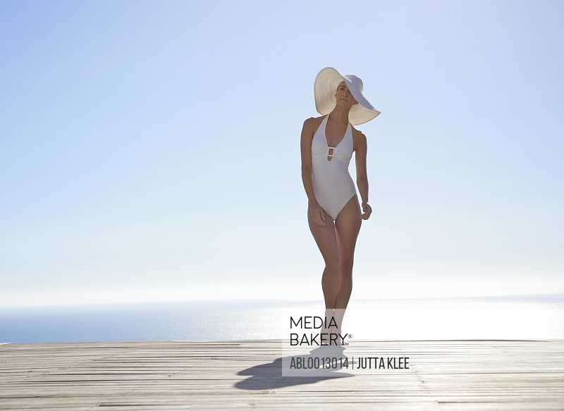 Woman in white hat and swimsuit standing on a sun deck