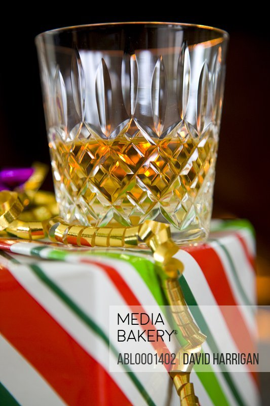 Close up of a glass of whiskey on a gift box