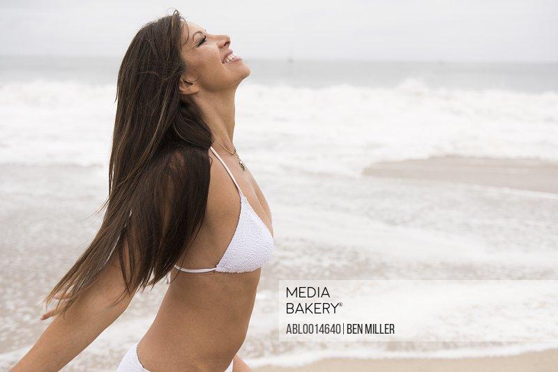 Woman Wearing Bikini Standing on Beach Smiling